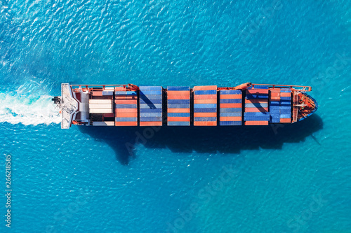 Fotografía  Cargo ship with containers against the blue sea, top view aerial
