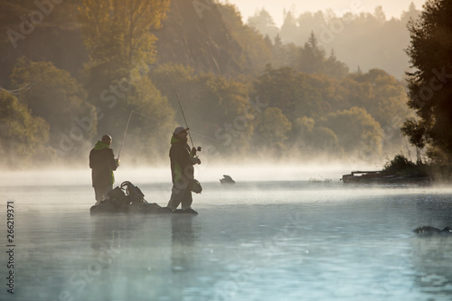 Photo Men fishing in river with fly rod during summer morning.