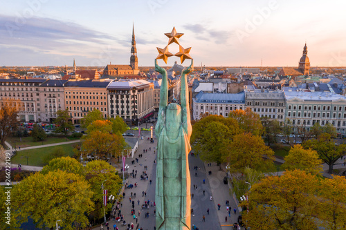 Beautiful sunset view over Riga by the statue of liberty - Milda in Latvia. The monument of freedom. People gathering around the monument for the concert.