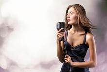 Young Woman Singing With Micro...