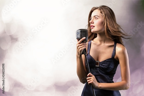 Young woman singing with microphone on blurred background Wallpaper Mural