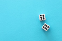 Rolling Dices Over Blue Background. Casino Gambling Concept