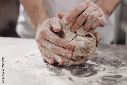 Fototapeta Professional baker kneads dough on the table in the kitchen of the bakery