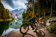 Leinwandbild Motiv Couple cycling on electric bike, rides mountain trail. Woman and Man riding on bikes in Dolomites mountains landscape. Cycling e-mtb enduro trail track. Outdoor sport activity.