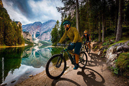 obraz lub plakat Couple cycling on electric bike, rides mountain trail. Woman and Man riding on bikes in Dolomites mountains landscape. Cycling e-mtb enduro trail track. Outdoor sport activity.