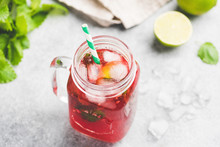 Berry Ice Tea With Glass Cup With Green Drinking Straw On Concrete Background. Refreshing Summer Cold Drink