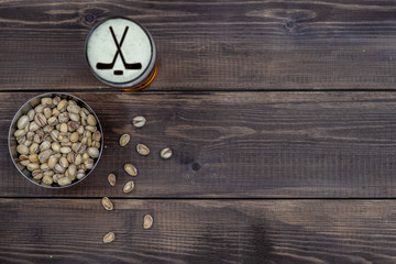 Beer and pistachios on dark wooden background. Top view. Empty space for text