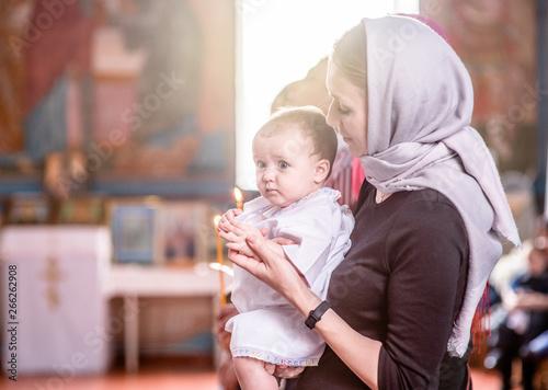Fotografiet Woman baptizes a child in church