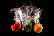 Fresh Green, Yellow And Red Bell Peppers With Water Splash And Bubble Isolated. Colorful Copy Space. Colored Paprika Dropped Into Water On Black Background