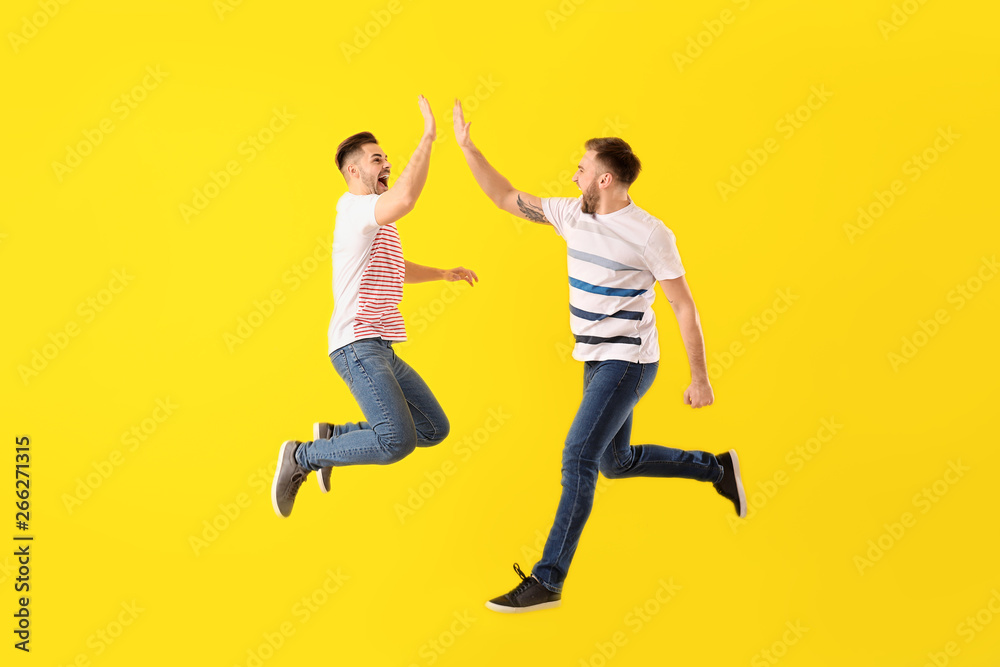 Fototapety, obrazy: Jumping young men on color background
