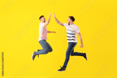 Jumping young men on color background Canvas Print