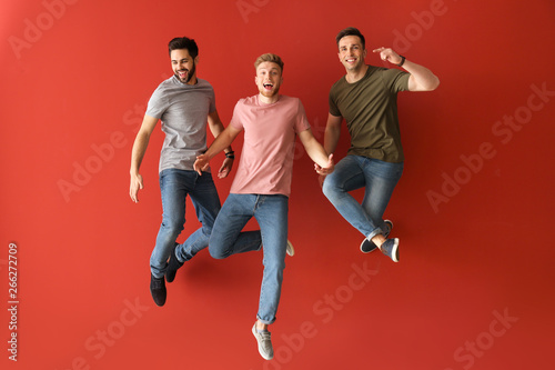 Jumping young men on color background