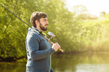a man on a Sunny day goes fishing, holding a fishing rod on his shoulder