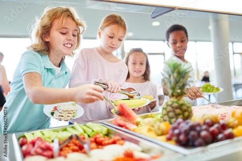 Photo  Hungrige Kinder holen sich Obst am Büffet