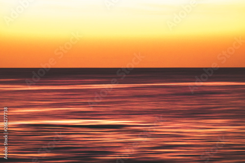 Foto auf Leinwand Rotglühen Artistic view of ocean sea water in long exposure in motion - background and coulours for nature concept - outdoors holiday vacation