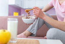 Woman In Pajamas Eating Frosted Chocolate Balls, Yellow Apple And Drinking Fresh Glass Of Milk For Healthy  Breakfast At Home