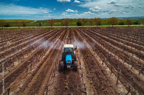 Fotografia  Aerial view of tractor spraying vineyard with fungicide.