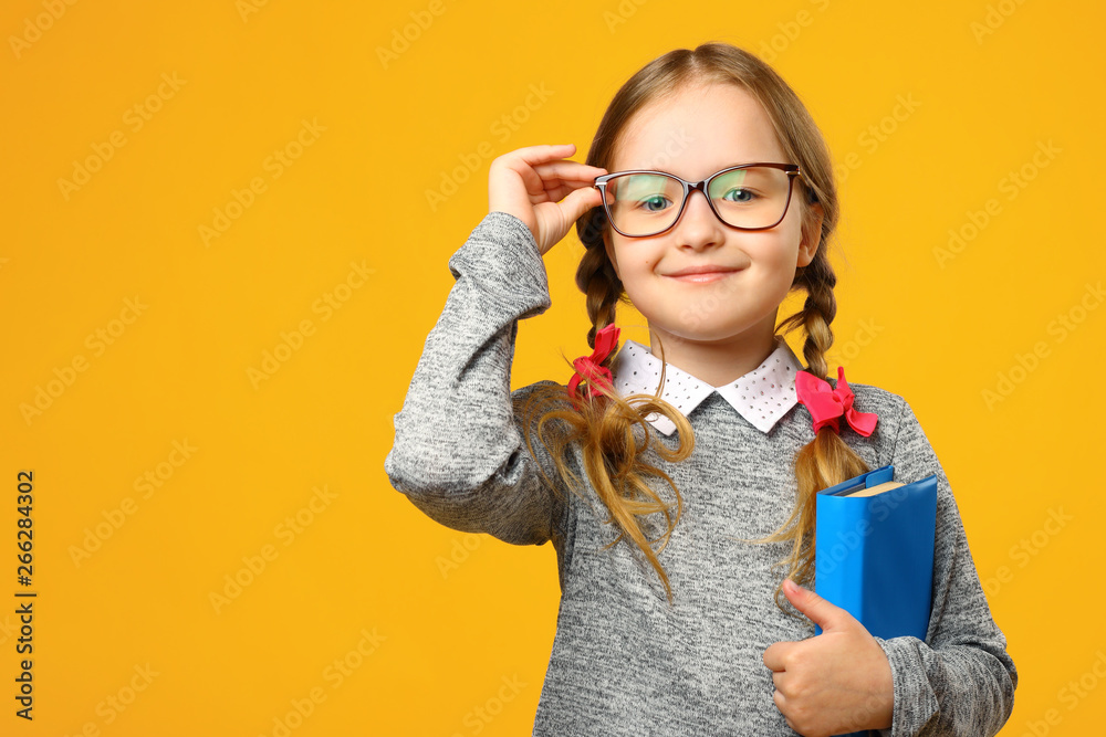Fototapety, obrazy: Portrait of a cute little kid girl on a yellow background. Child schoolgirl looking at the camera, holding a book and straightens glasses. The concept of education. Copy space.