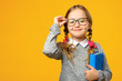 Leinwandbild Motiv Portrait of a cute little kid girl on a yellow background. Child schoolgirl looking at the camera, holding a book and straightens glasses. The concept of education. Copy space.