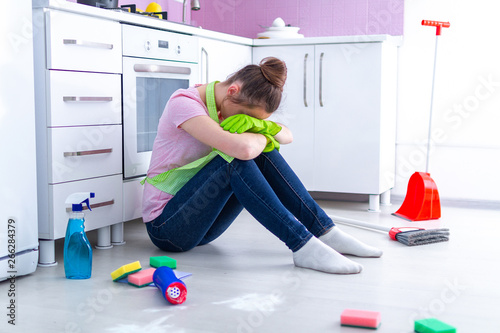 Fotografie, Obraz  Young overworked housewife is tired of household chores and spring cleaning at kitchen at home