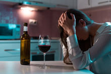 Unhappy, Lonely, Young Woman With Red Wine Is Drinking Alone At Home In Evening. Life Difficulties And Problems. Female Alcoholism And Alcohol Addiction