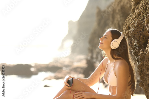 Relaxed sunbather listens to music on the beach - 266285923