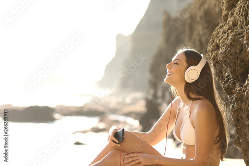 Relaxed tourist in bikini listening to music on the beach - 266285933