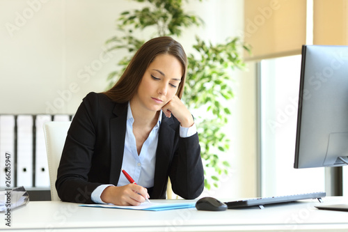 Fototapety, obrazy: Serious office worker writing on document