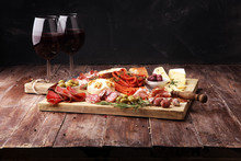 Cutting Board With Prosciutto, Salami, Cheese,bread And Olives On Dark Wooden Background