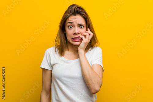 Canvas Print Young natural caucasian woman biting fingernails, nervous and very anxious