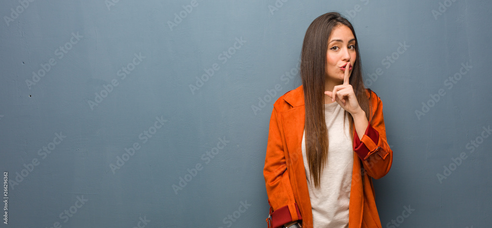 Fototapeta Young natural woman keeping a secret or asking for silence