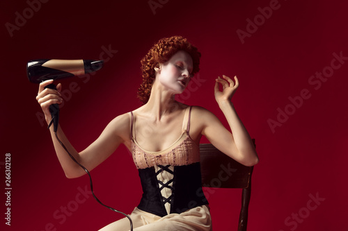 Medieval redhead young woman as a duchess in black corset and night clothes sitting on the chair on red background Fototapeta