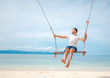 Young handsome attractive latin man rolling on a swing against the backdrop of a tropical beach and sea, vacations and travels