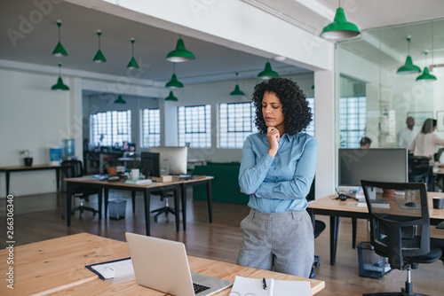 Young businesswoman standing in an office looking deep in thought