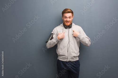 Fotomural  Young fitness redhead man surprised, feels successful and prosperous