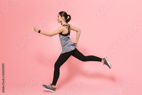 Beautiful young pretty fitness woman running make sport exercises isolated over pink wall background. - 266314190
