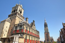 The External Facade Of The Town Hall (rebuilt In 1629) On The Left And The Clock Tower Of Nieuwe Kerk On The Right, Delft, Netherlands