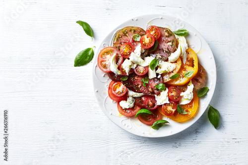 Fototapeta Mixed tomato salad with mozzarella cheese and basil leaves. Mediterranean cuisine obraz