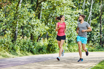 Happy couple running in park