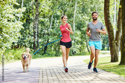 Fotografie, Obraz  Happy couple running with dog in park