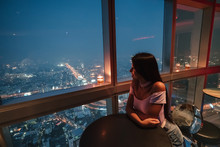 View Of The Modern Metropolis At Night. Bangkok, Thailand. The Girl Is Enjoying A Delicious Cocktail At The Bar On The 86th Floor.