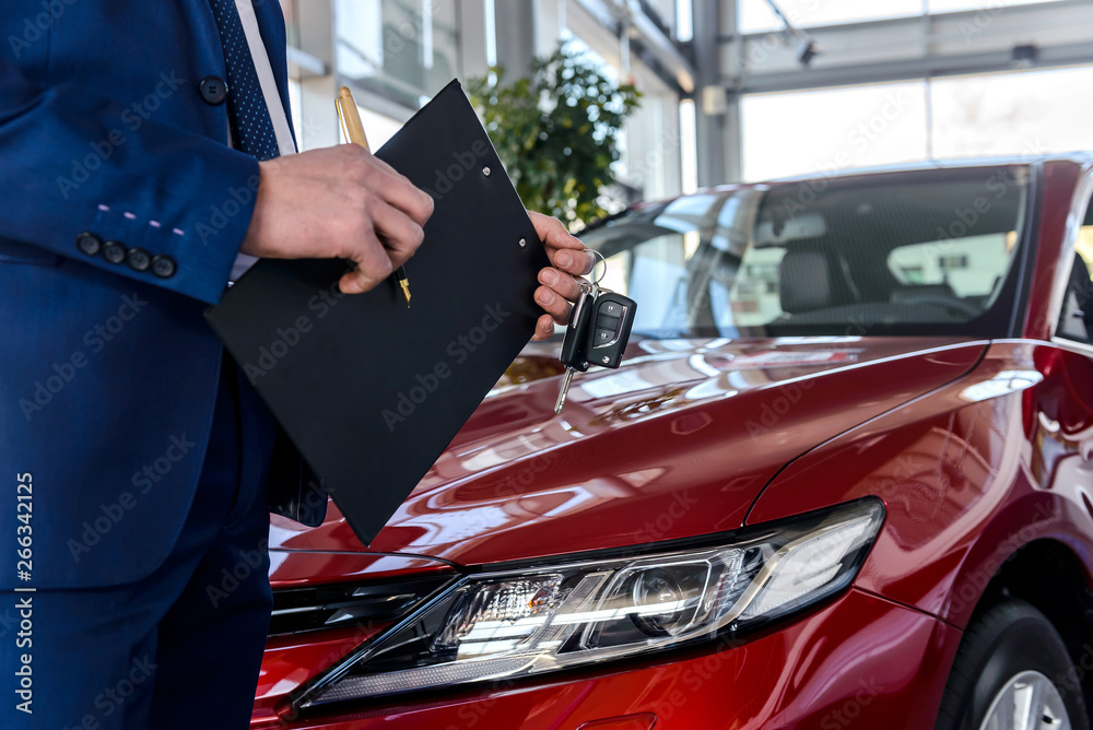 Fototapety, obrazy: Young car dealer holding clipboard in salon