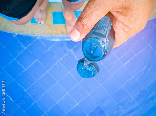 Swimmer\'s hand holds the swimming goggles on the pool edge ...