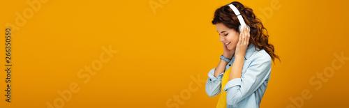 Fotografia panoramic shot of happy redhead girl listening music in headphones on orange