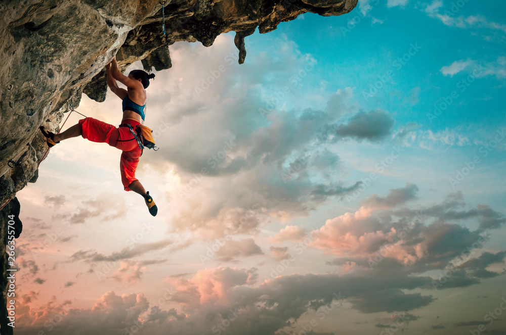 Fototapeta Athletic Woman climbing on overhanging cliff rock with sunrise sky background