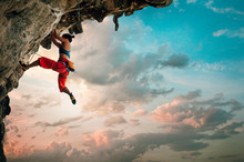 Athletic Woman Climbing On Overhanging Cliff Rock With Sunrise Sky Background