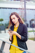 canvas print picture - Businesswoman with a mobile phone in the street with office buildings in the background