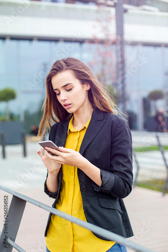 canvas print motiv - Boggy : Businesswoman with a mobile phone in the street with office buildings in the background