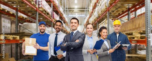 logistic business, delivery service and people concept - happy international team of employees over warehouse background