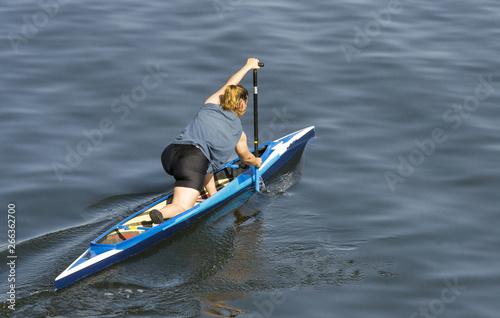 Valokuvatapetti giovane ragazza in pantaloncini che rema in canoa